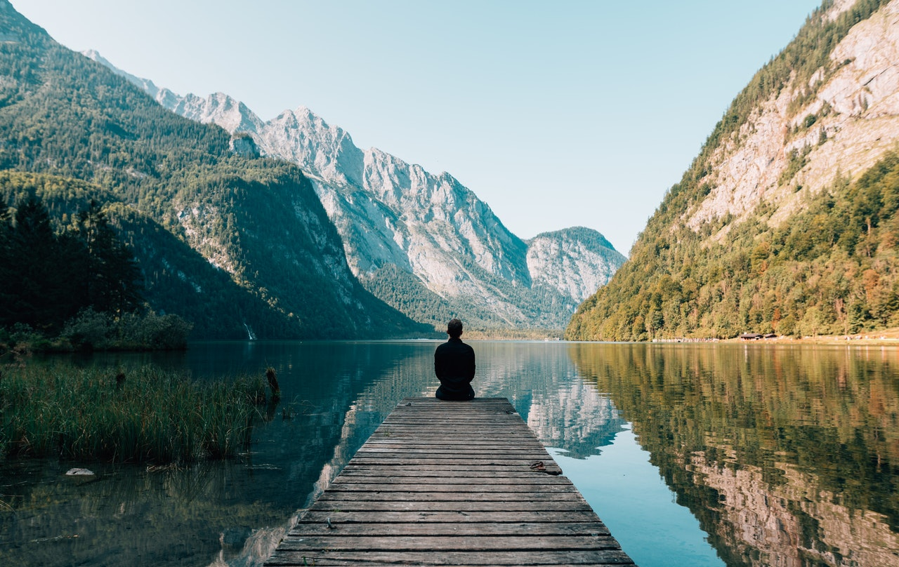 A person sits on the edge of a lake looking out to mountains