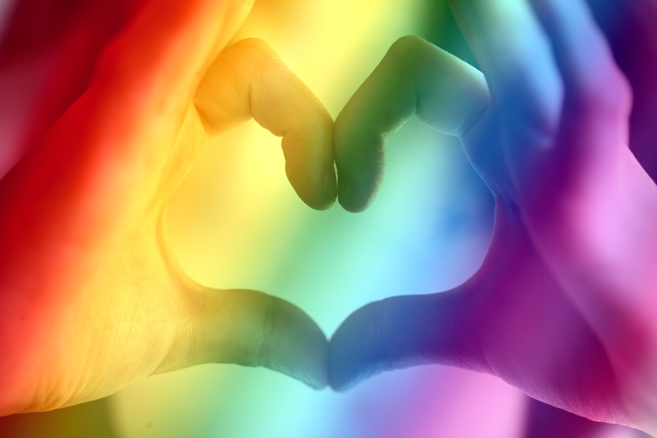 Hands making a heart shape coloured as a rainbow