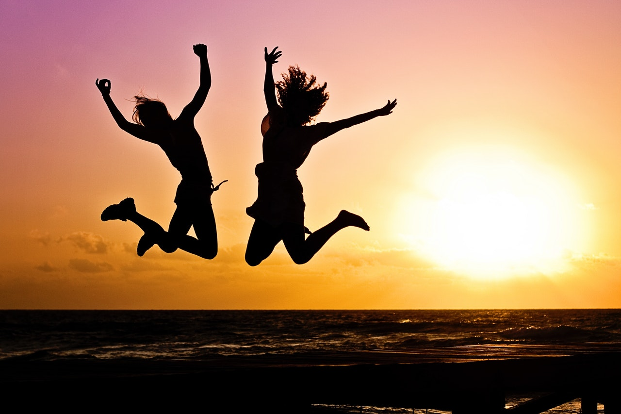Two people jump in to the air at sunset to represent the positivity around SOAR Analysis