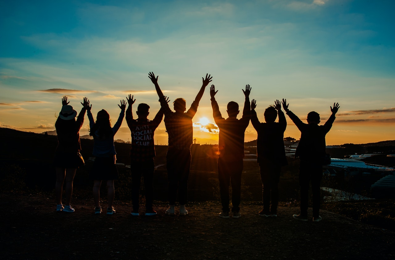 A team of people raise their hands at sun set