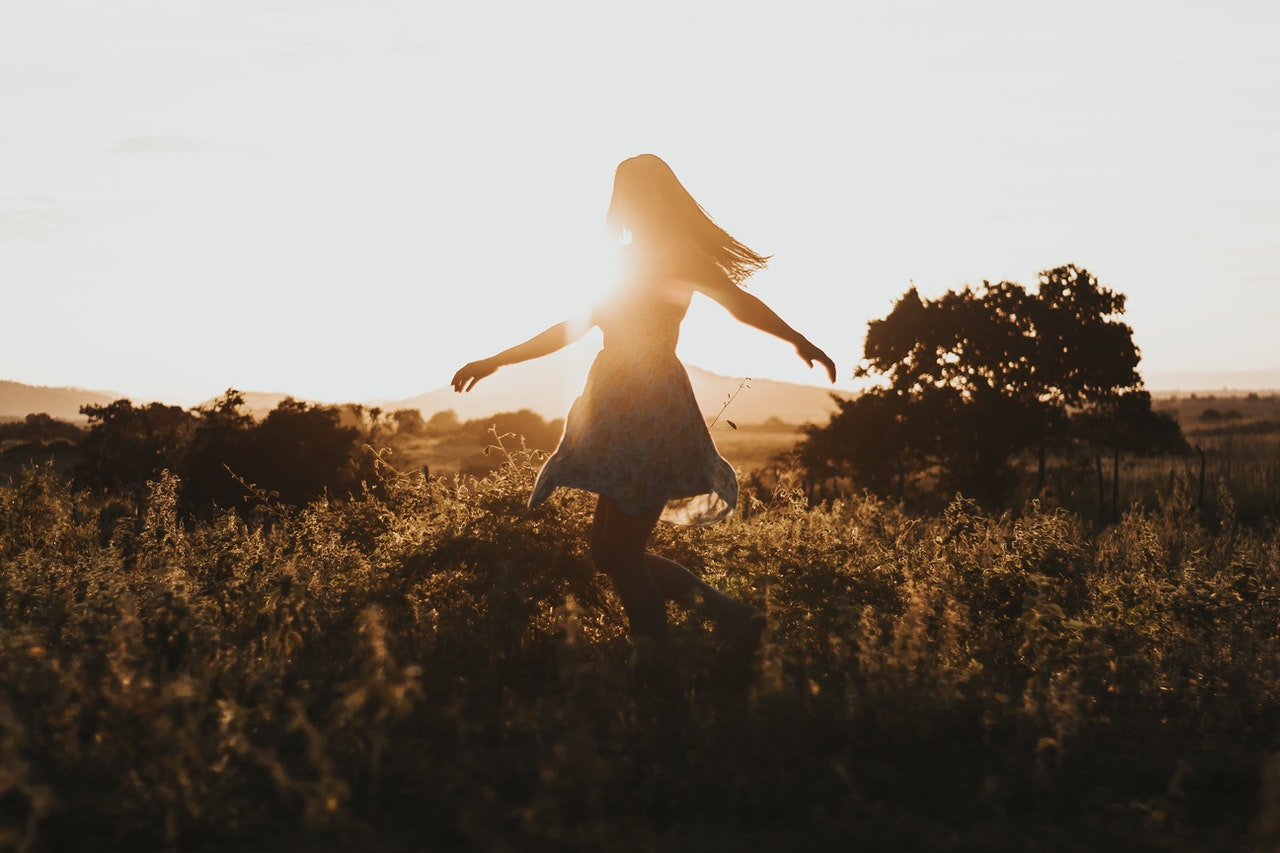 A girl walking through a field in the early morning sun