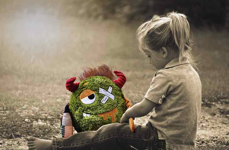 A injured toy monster is looked after by a young girl
