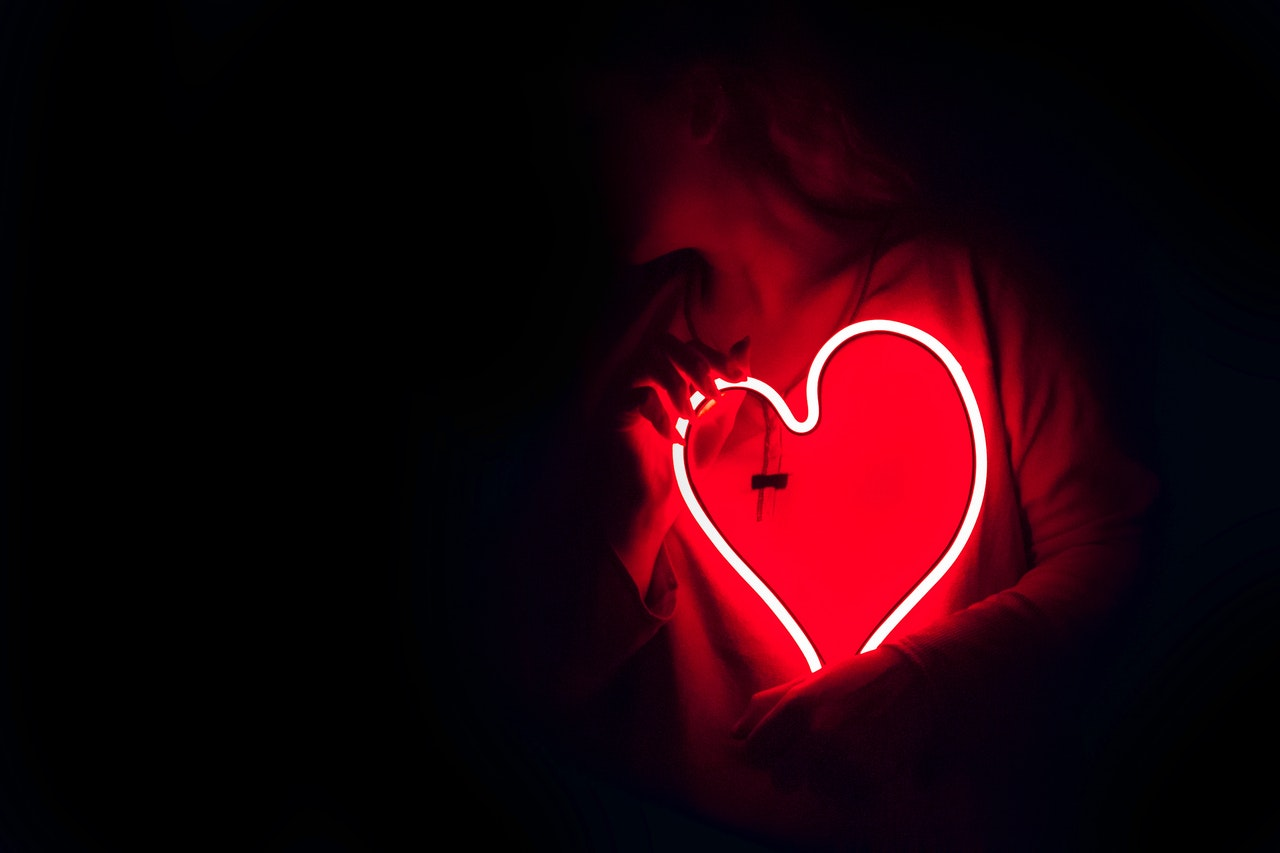 A red heart lit up on a dark background