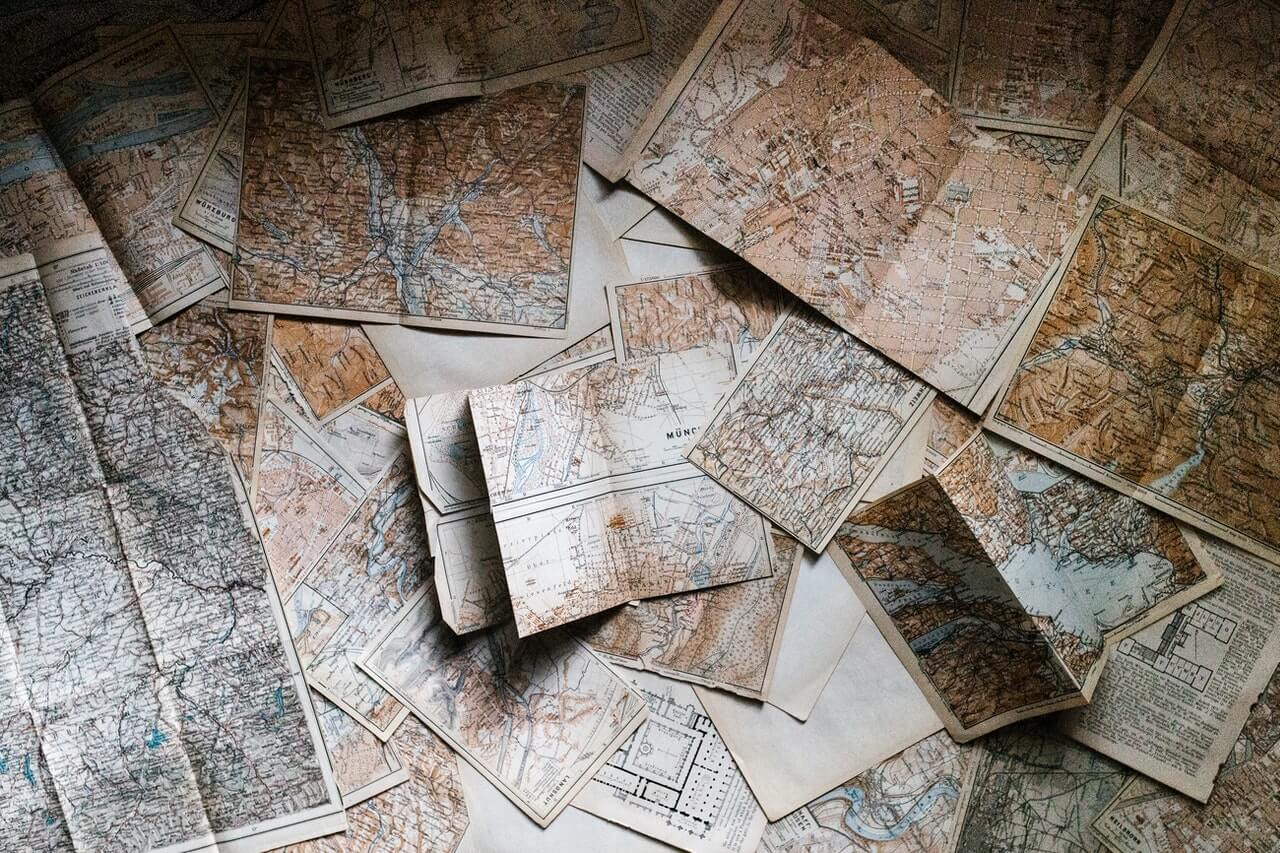Lots of maps on a desk to represent The Strategy Map