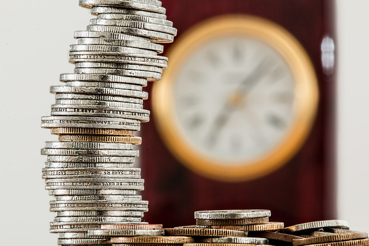 Pile of coins in front of a clock