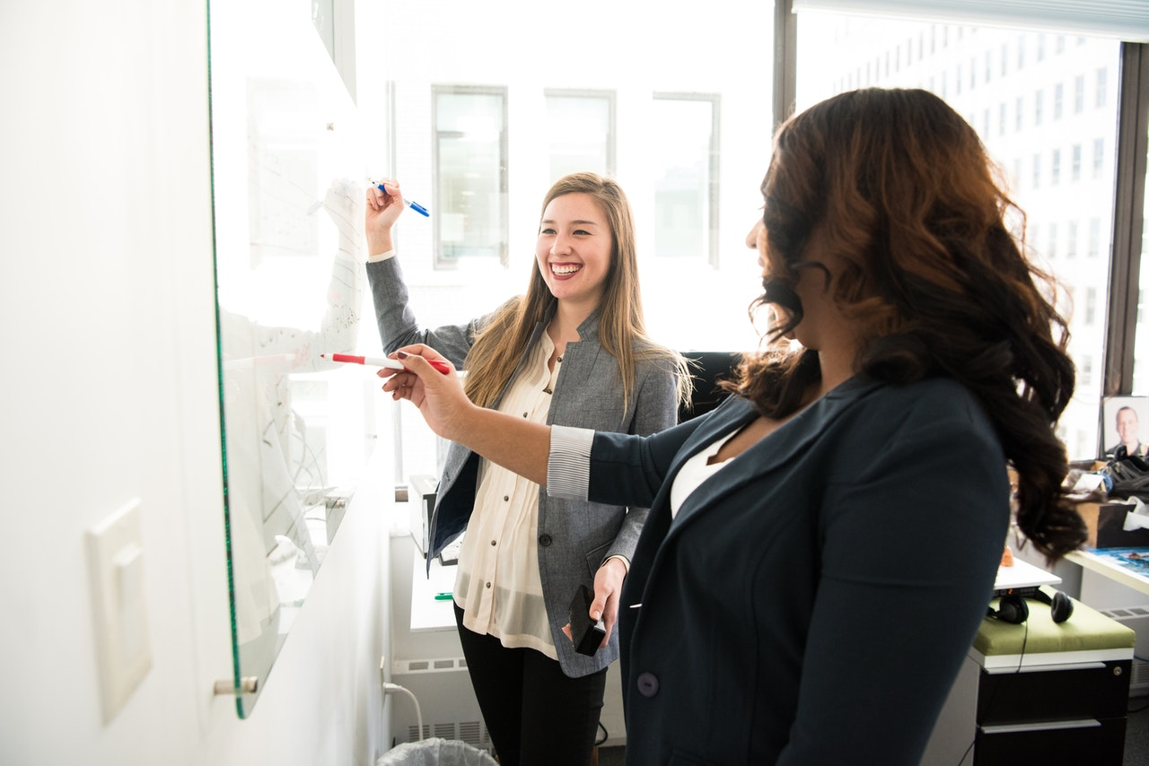 Two women working on a whiteboard