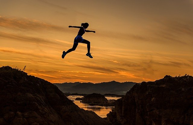 Woman jumping across a wide gap to suggest the execution gap in strategy