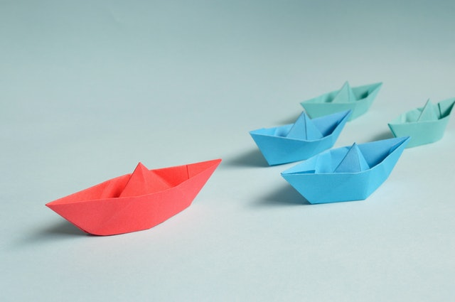 paper boat leading other paper boats to represent business leadership